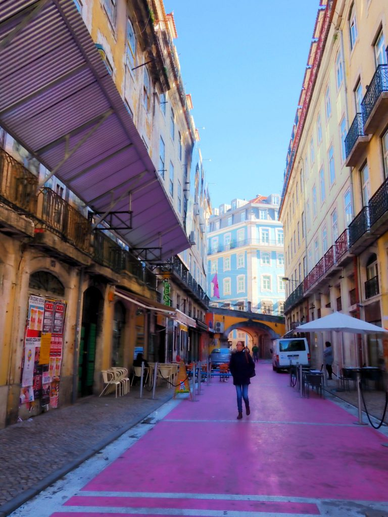 Women walking through the pink street in Lisbon, Portugal