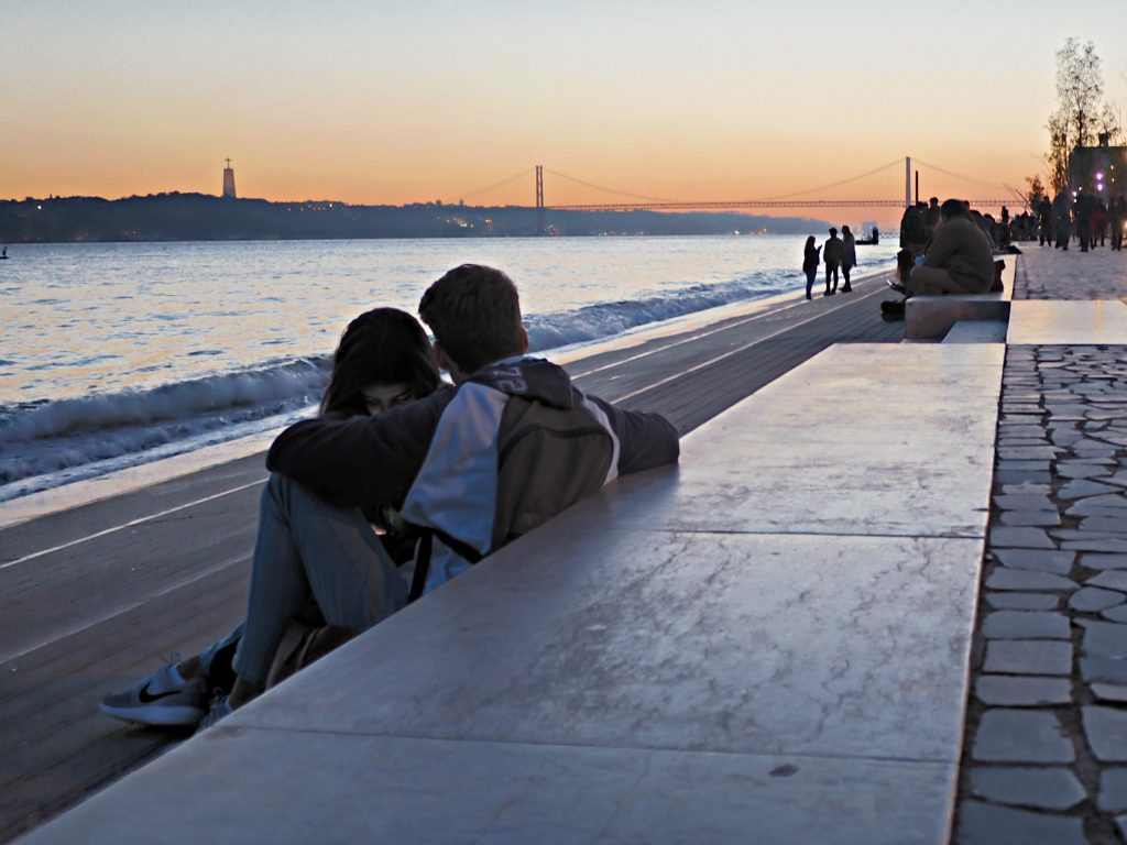 A couple looking at the sunset over the 25th of April bridge in Lisbon, Portugal