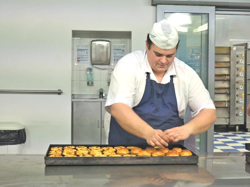 a cooc is preparing the traditional pastel de nata in Belem, Lisbon, Portugal