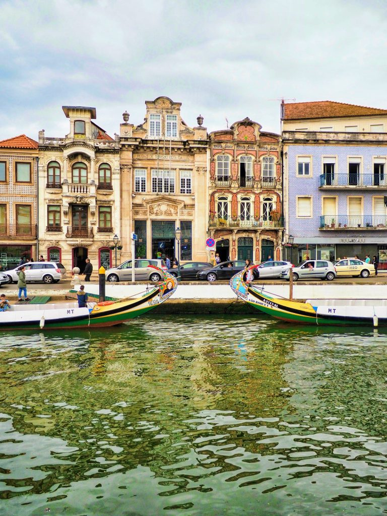 The main canal of Aveiro with some Moliceiros or traditional boats and Rococco buildings on the backdrop, Portugal