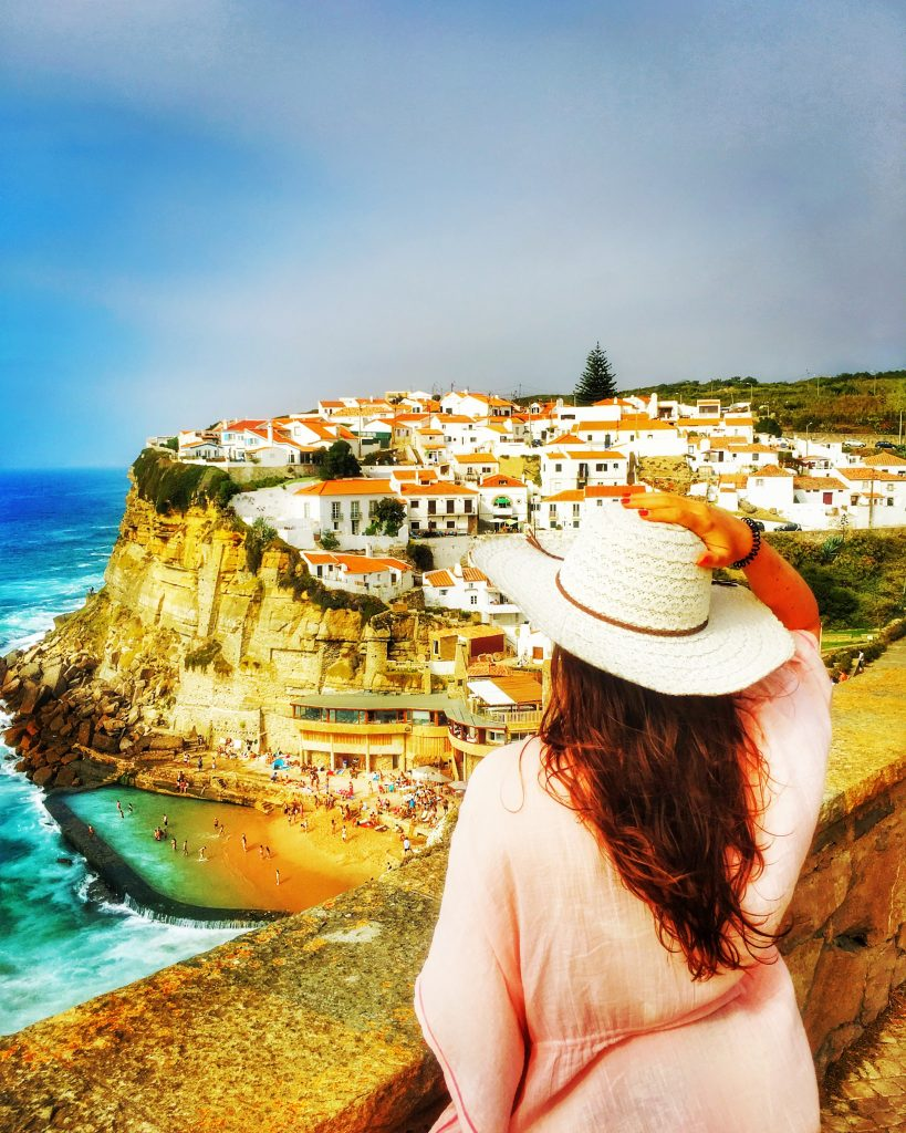A girl looking at Azenhas do Mar prettu village.