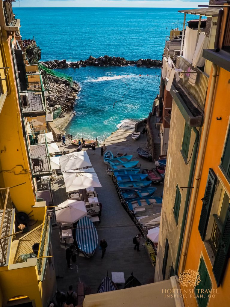 Riomaggiore village in Cinque terre with blue boats and yellow buildings